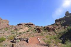 户外远足与太阳的人们一个沙漠山行迹日间发光 免版税库存图片