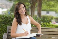 户外长凳的年轻成年女性学生 图库摄影