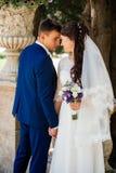 户外雍美好的新娘和新郎拥抱 新娘拥抱新郎 在爱的夫妇婚礼之日 免版税图库摄影