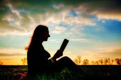 户外青少年的女孩阅读书 免版税库存照片