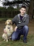 户外青少年的男孩与黄色实验室 免版税库存图片