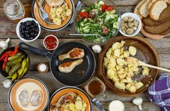 户外食物概念 开胃烤鸡腿、芯片和新鲜蔬菜沙拉在一张木野餐桌上的 图库摄影
