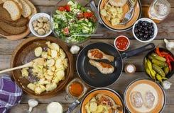 户外食物概念 开胃烤鸡腿、芯片和新鲜蔬菜沙拉在一张木野餐桌,顶视图上的 免版税库存图片
