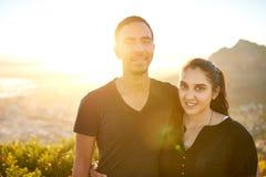 户外年轻不同种族的夫妇与太阳火光 库存照片