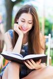 户外读妇女年轻人的书 库存照片