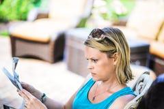户外读报纸的白肤金发的妇女 免版税库存图片