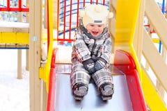 户外幻灯片的滑稽的婴孩在冬天 免版税库存图片
