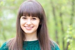 户外年轻美丽的妇女深色的女孩在夏天绿色背景的愉快的微笑的&看的照相机特写镜头画象  免版税库存图片
