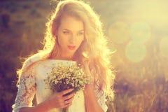 户外年轻美丽的新娘在日落 免版税库存图片