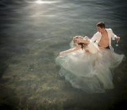 户外年轻美好的新娘夫妇在岩石水池 免版税图库摄影