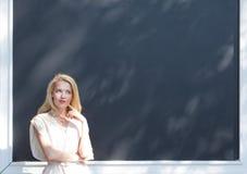 户外画象一个热的夏日美丽的性感的金发碧眼的女人的在墙壁背景的一个沉思姿势的与框架 免版税库存图片