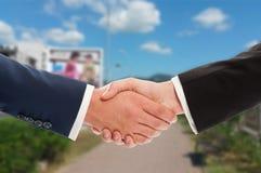 房地产在土地和天空背景的销售握手 库存照片