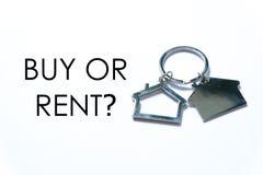 房地产或物产题材 在白色背景的议院钥匙链写与问题购买或租? 库存图片