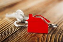 房地产概念,与房子标志木backgtound的红色keychain 免版税库存图片