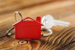 房地产概念,与房子标志木backgtound的红色keychain 库存照片