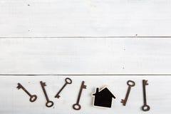 房地产概念-一点房子和钥匙在白色木书桌上 免版税库存图片