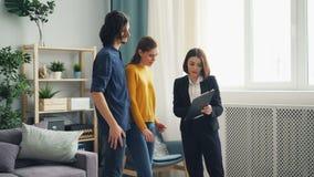 房地产经纪人谈话与显示纸的快乐的客户户内在公寓 影视素材