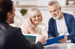 房地产顾问与年迈的夫妇一起使用在房子里 库存照片