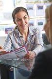 房地产经纪商谈论物产与客户在办公室 库存图片