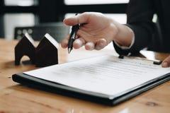 房地产经纪商需要签署协议以他的顾客 库存照片