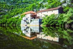 房子、森林、绿色灌木和岩石的美好的反射在水斯库台湖,巴尔干半岛,黑山中 免版税库存照片