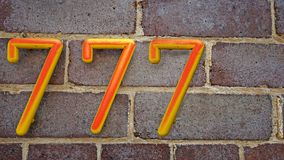房子号码七百和七十七777在砖墙背景 免版税图库摄影