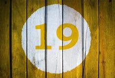 房子号码或历日在白色圈子在被定调子的黄色 免版税库存图片