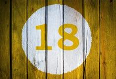 房子号码或历日在白色圈子在被定调子的黄色 库存照片