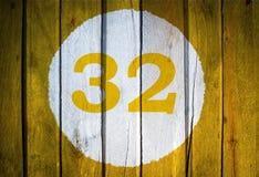 房子号码或历日在白色圈子在黄色被定调子的wo 免版税库存图片