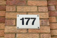 房子号码177标志固定在墙壁 库存照片
