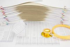 房子和黄色和金听诊器破产  免版税库存图片