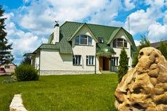 房子在绿色屋顶下。 库存图片