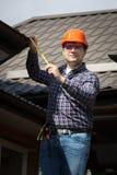 房子屋顶的安全帽测量的大小的工作者 免版税图库摄影