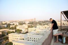 从房子屋顶的阿拉伯埃及年轻商人 库存图片