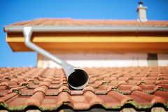 房子屋顶细节有喷水嘴和小烟囱的 库存照片
