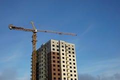 房子建设中和在蓝天旁边的一台建筑用起重机 免版税图库摄影