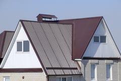 房子是与顶楼和一个联合的屋顶 有塑料窗口和波纹状的板料一个棕色屋顶的议院  免版税库存照片