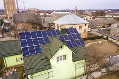 房子村庄鸟瞰图与蓝色发光的太阳照片流电盘区系统的在屋顶 可更新的生态绿色能量 免版税库存照片
