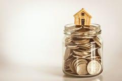 房子模型地方的关闭堆积的一笔房屋贷款和贷款,重新贷款或物产投资概念的金钱硬币 库存照片