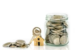 房子模型地方的关闭堆积的一笔房屋贷款和贷款,重新贷款或物产投资概念的金钱硬币 库存图片