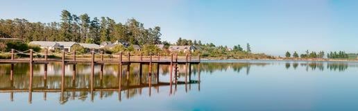 房子清早全景在水坝旁边的 库存图片