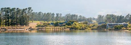 房子清早全景在水坝旁边的 免版税库存图片