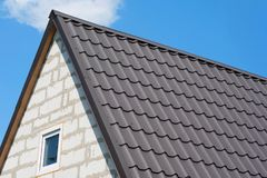 房子的屋顶在棕色木瓦下的 未完成的房子关闭的角落,以天空蔚蓝为背景 库存图片