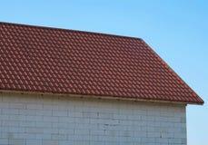 房子的屋顶在红色木瓦下的 以天空蔚蓝为背景的议院细节 免版税库存照片