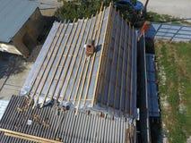房子的屋顶的修理 在金属下的湿气绝缘材料 免版税图库摄影
