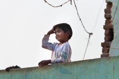 房子的屋顶的印地安年轻男孩 图库摄影