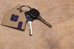 房子的标志有钥匙的在木背景 库存图片