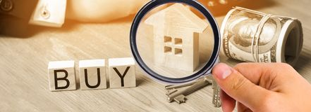 房子的模型,钥匙、美元和题字`买在木块的` 公寓的购买,物产 付得起的housi 图库摄影