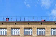 房子的砖门面有一个屋顶和白色窗口的反对蓝天 免版税库存照片