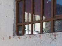 房子的窗口在白色墙壁上的:棕色木制框架,强光反射晚上太阳和蓝天 免版税库存照片